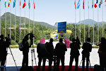 Journalist take pictures outside the venue of a summit at the Belt and Road Forum in Beijing