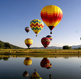 Balloons fly in the sky as their reflections are cast down onto Bald Eagle Lake during the 36th Annual Hot Air Balloon Rodeo in Steamboat Springs, Colorado