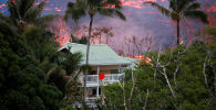 Lava flows near a house on the outskirts of Pahoa during ongoing eruptions of the Kilauea Volcano in Hawaii, U.S., May 19, 2018.