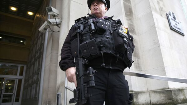 An armed police officer stands guard outside of the Ministry of Defence in London, Britain November 18, 2015 - Sputnik Узбекистан