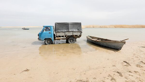Fishermen ride in a truck to collect fish from a boat in shallow water by the Aral Sea, outside the village of Karateren, south-western Kazakhstan, April 15, 2017. Akespe, home to some 250 people, and Karateren, inhabited by about 150, used to be dominated by fishermen until the water receded too far away - but it is now back in Karateren - Sputnik Узбекистан