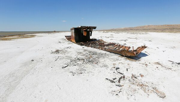 A ruined ship lays on a salinated part of the Aral Sea coastline near the village of Akespe, south-western Kazakhstan, April 16, 2017. Akespe, home to some 250 people, and Karateren, inhabited by about 150, used to be dominated by fishermen until the water receded too far away - but it is now back in Karateren. - Sputnik Узбекистан