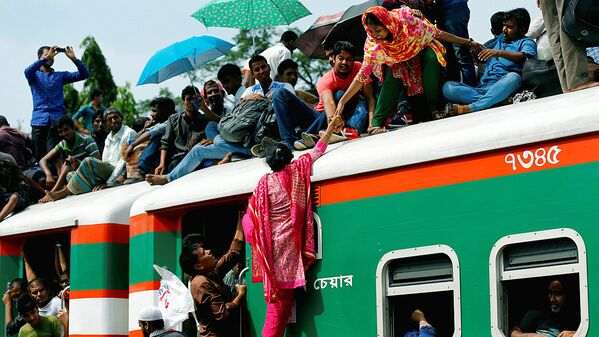 A woman helps another woman to get atop of an overcrowded passenger train as they travel home to celebrate Eid al-Fitr festival at a railway station in Dhaka - Sputnik Узбекистан