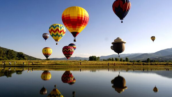 Balloons fly in the sky as their reflections are cast down onto Bald Eagle Lake during the 36th Annual Hot Air Balloon Rodeo in Steamboat Springs, Colorado - Sputnik Узбекистан