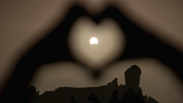 A woman makes a heart shape with her hands during a partial eclipse of the sun over the Roque Nublo mountain at the Canary Island of Gran Canaria - Sputnik Узбекистан