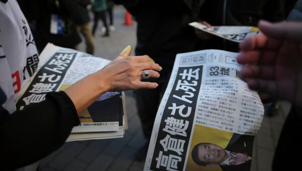 A worker, bottom, distributes an extra edition of a newspaper with front page featuring an obituary notice of acclaimed Japanese film star Ken Takakura at Shimbashi Station in Tokyo, Tuesday, Nov. 18, 2014 - Sputnik Узбекистан